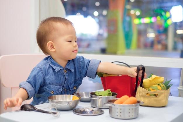 Милый маленький азиатский мальчик развлекается, играя в одиночестве с кулинарными игрушками в игровой школе Premium Фотографии