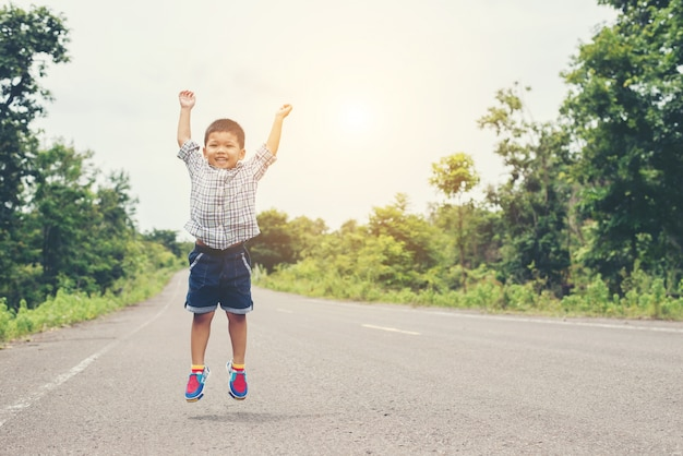 Cute little asian boy jumping on the road. Free Photo