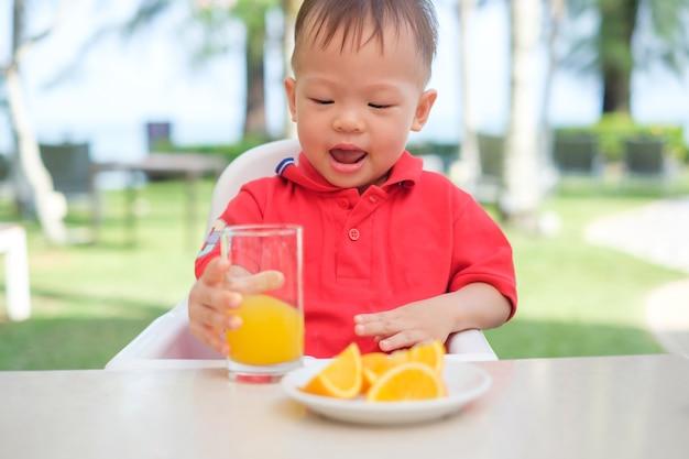 朝食時にガラスでおいしいオレンジジュースの冷たい飲み物を保持&飲む高い椅子に座っているかわいい小さなアジア幼児男の子 Premium写真