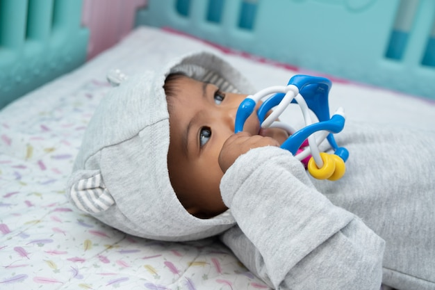 Cute little asin baby boy lying on soft blanket and play toy Premium Photo