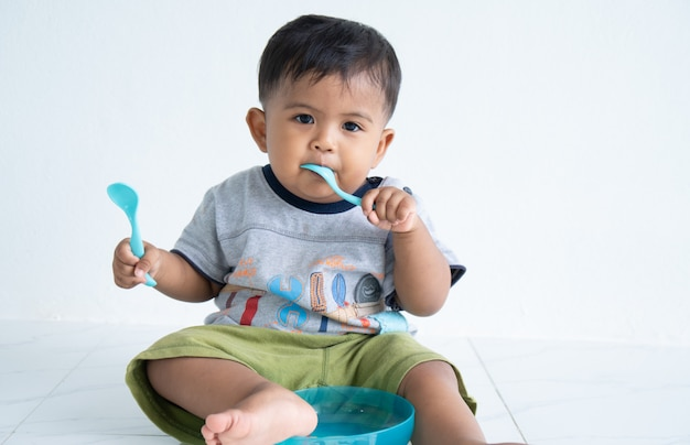 Cute little asin baby boy with spoon Premium Photo
