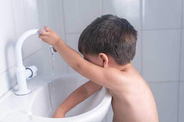 Piccolo neonato sveglio che lava la mano nel lavandino del bagno Foto Gratuite