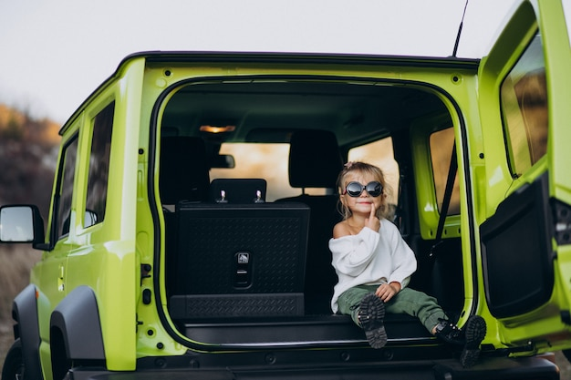 Cute little baby girl sitting in the back sit of the car Free Photo