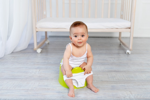 Cute little baby girl sitting on a potty Premium Photo