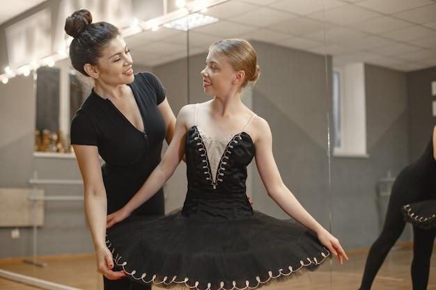 검은 발레 의상을 입은 귀여운 작은 발레리나. 젊은 아가씨가 방에서 춤을 추고 있습니다. 교사와 댄스 클래스에서 소녀입니다. 무료 사진