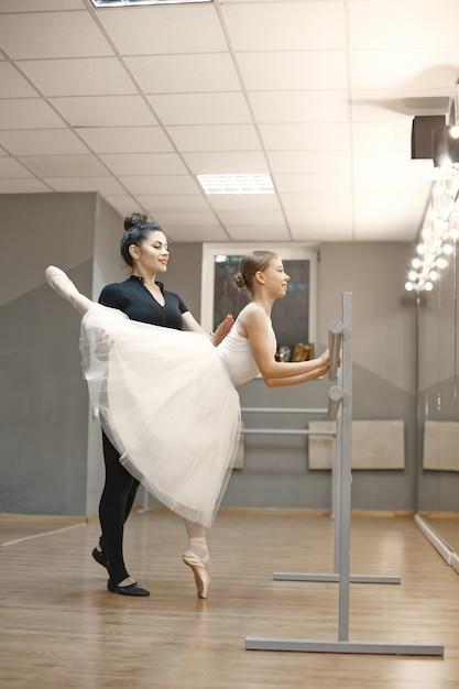 흰색 발레 의상을 입은 귀여운 작은 발레리나. 젊은 아가씨가 방에서 춤을 추고 있습니다. 교사와 댄스 클래스에서 소녀입니다. 무료 사진