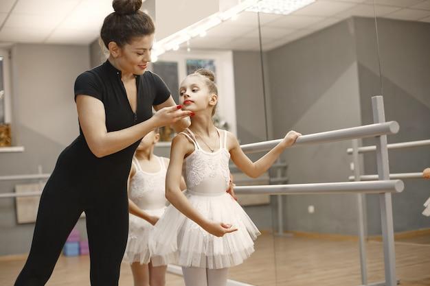 핑크 발레 의상을 입은 귀여운 작은 발레리나. 뾰족 구두를 신은 아이들이 방에서 춤을 추고 있습니다. 선생님과 함께 댄스 클래스에서 아이. 무료 사진
