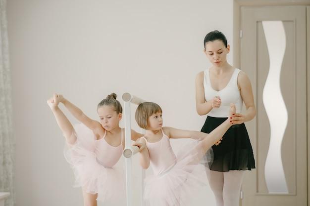 ピンクのバレエ衣装のかわいい小さなバレリーナ。トウシューズを履いた子供たちが部屋で踊っています。ティーチャーとダンスクラスの子供。 無料写真