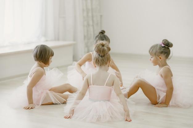ピンクのバレエ衣装のかわいい小さなバレリーナ。トウシューズを履いた子供たちが部屋で踊っています。ダンスクラスの子供。 無料写真