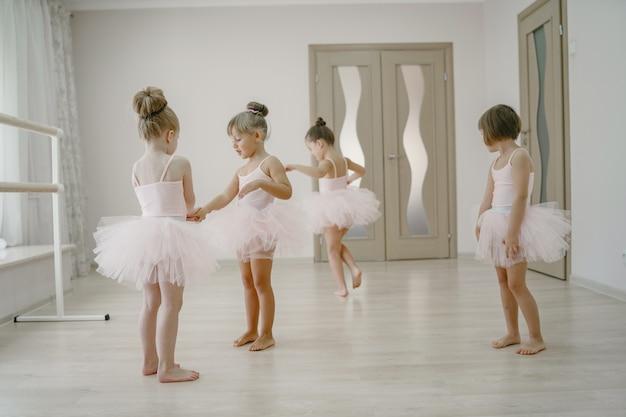 ピンクのバレエ衣装のかわいい小さなバレリーナ。トウシューズを履いた子供たちが部屋で踊っています 無料写真