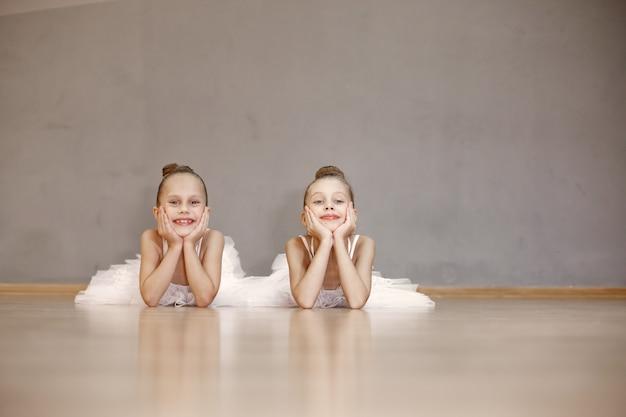 흰색 발레 의상을 입은 귀여운 작은 발레리나. 뾰족 구두를 신은 아이들이 방에서 춤을 추고 있습니다. 댄스 클래스에서 아이. 무료 사진