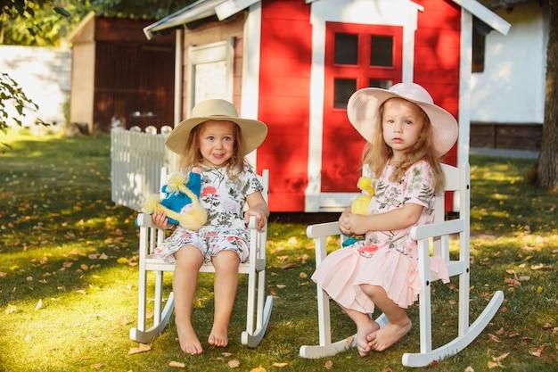 夏の柔らかいおもちゃでフィールドに座っている帽子のかわいい金髪の女の子。 無料写真
