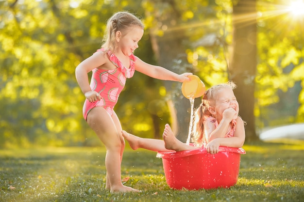 The cute little blond girls playing with water splashes on the field in summer Free Photo