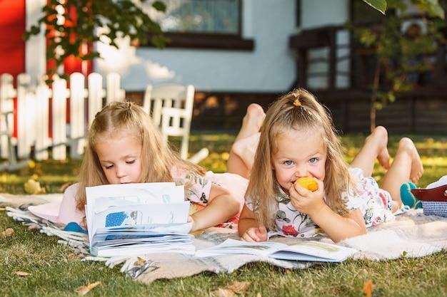 Симпатичные маленькие белокурые девочки, читающие книгу снаружи на траве Бесплатные Фотографии