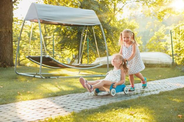 Симпатичные маленькие белокурые девочки езда игрушечный автомобиль летом. Бесплатные Фотографии
