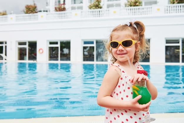 Симпатичная маленькая блондинка у бассейна и держит в руках коктейль. Бесплатные Фотографии
