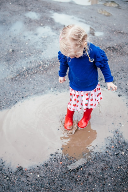 Cute little blonde girl wearing red rain boots jumping into a puddle Premium Photo
