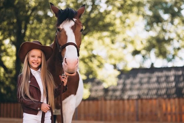 Cute little blonde girl with horse at ranch Free Photo