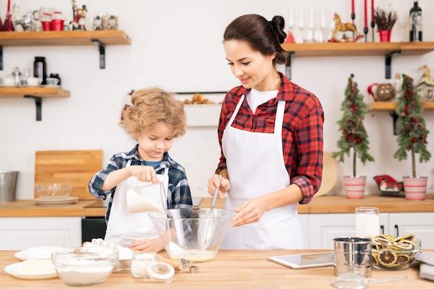 Симпатичный маленький мальчик добавляет сахар во взбитые сырые яйца в миске, помогая матери с тестом для домашней выпечки на кухне Premium Фотографии