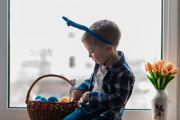 Cute little boy checking basket with eggs Free Photo