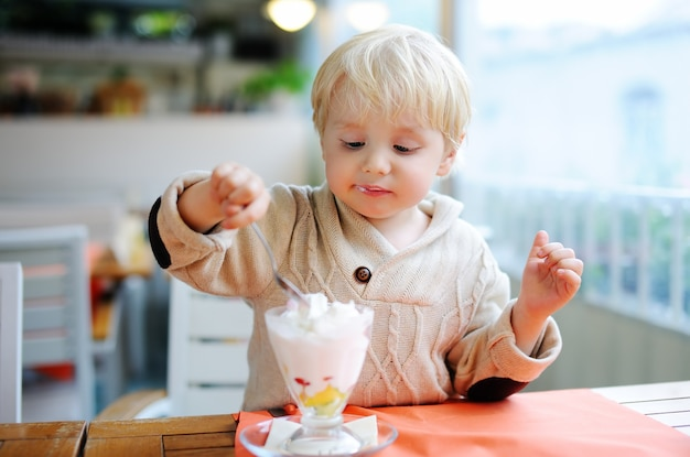 Cute little boy eating ice-cream (gelato) in italian indoors cafe. sweets/sugar food for little kids Premium Photo