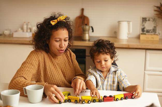 Cute little boy enjoying game sitting with his cheerful mother at kitchen table during breakfast. family portrait of young latin female playing with her adorable son. childhood, games and imagination Free Photo