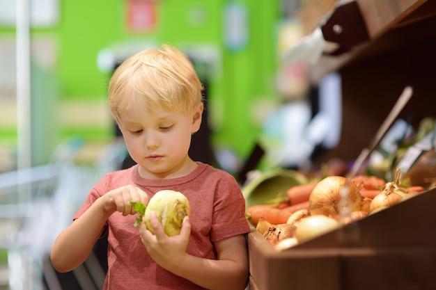 Cute little boy in a food store or a supermarket choosing fresh organic celery root Premium Photo