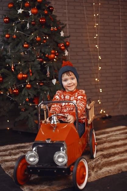 빨간 스웨터에 귀여운 작은 소년. 크리스마스 트리 자식입니다. 무료 사진