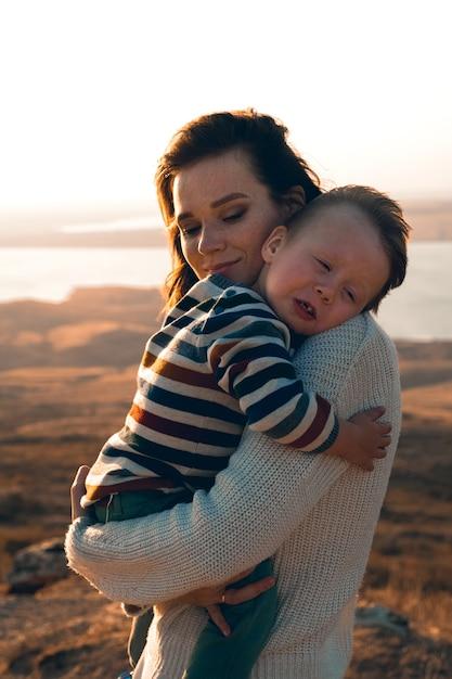 彼の母親の腕の中でかわいい男の子。彼女の生まれたばかりの息子を運ぶ家の女性。 Premium写真