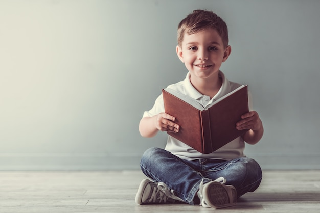 Cute little boy is holding a book, looking at camera. Premium Photo