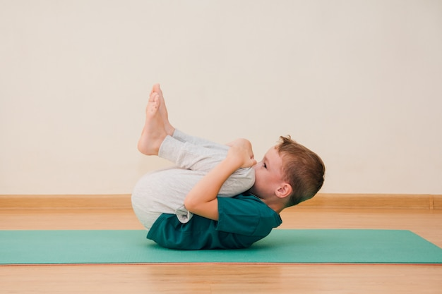 Cute little boy is learning to do yoga in the gym Premium Photo