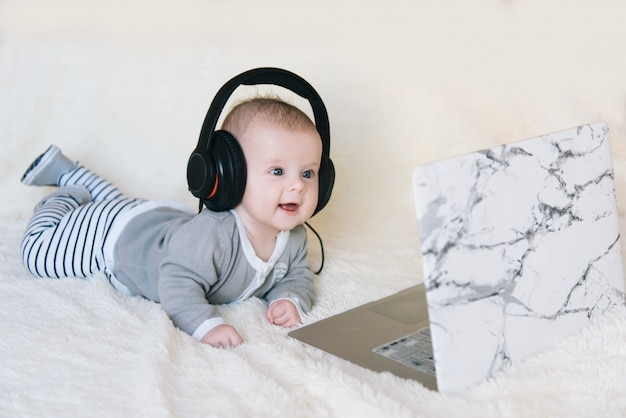 Cute little boy lies on his stomach in headphones and looks in laptop, selective focus Premium Photo