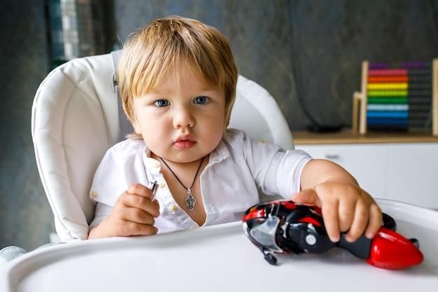 Милый маленький мальчик европейской внешности сидит на белом стуле и играет с игрушечным мотоциклом Premium Фотографии