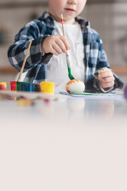 Cute little boy painting eggs for easter Free Photo