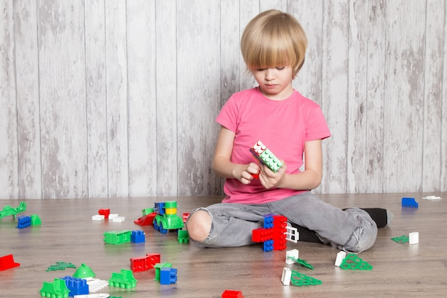 Cute little boy in pink t-shirt and grey jeans playing with toys Free Photo