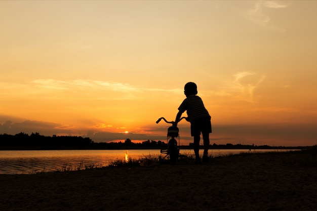 Cute little boy play and riding bicycle sunset background Premium Photo