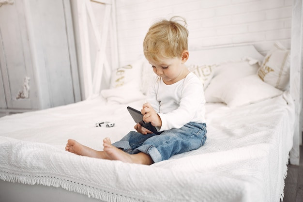 Cute little boy playing with a laptop on a bed Free Photo