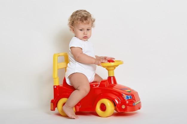 赤と黄色のおもちゃの車に乗って、目をそらし、裸足でポーズをとって、ボディースーツを着るかわいい男の子 Premium写真