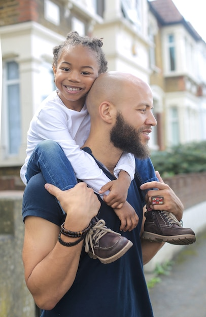 Cute little boy sitting on his father's shoulders Premium Photo
