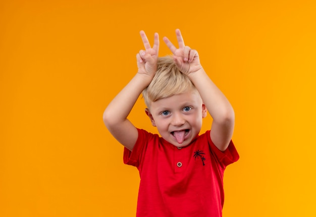 Un ragazzino sveglio con capelli biondi che indossa la maglietta rossa che tiene due dita sopra la sua testa su una parete gialla Foto Gratuite
