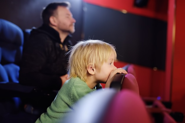 Cute little boy with his father watching cartoon movie in the cinema Premium Photo