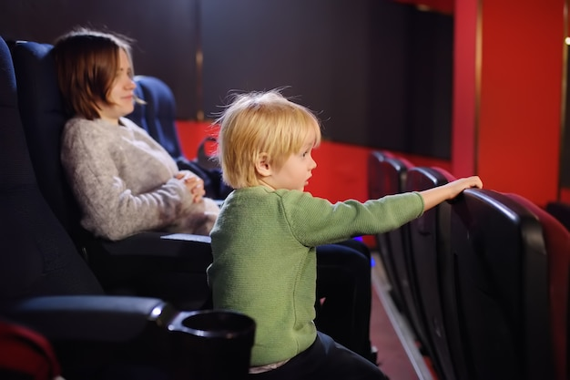 Cute little boy with his mother watching cartoon movie in the cinema Premium Photo