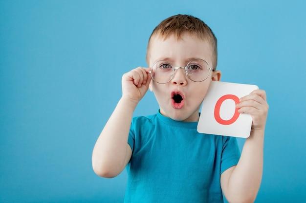 Милый маленький мальчик с письмом. ребенок учится буквы. алфавит Premium Фотографии
