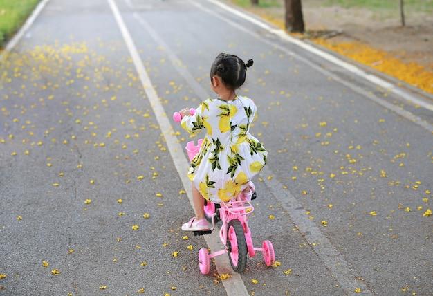 Cute little child girl riding bike in park. rear view. Premium Photo