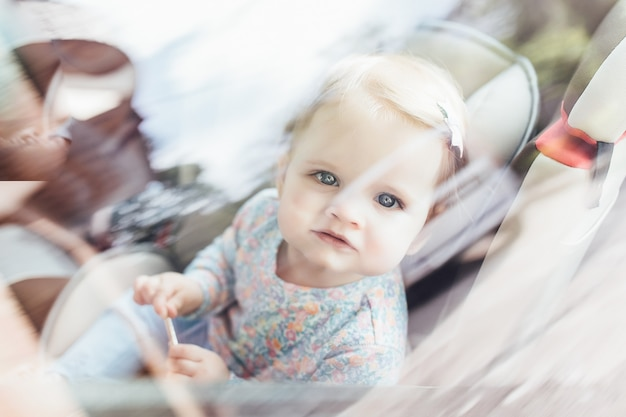 Cute little child girl sitting in safety seat inside car. danger prevention. Premium Photo