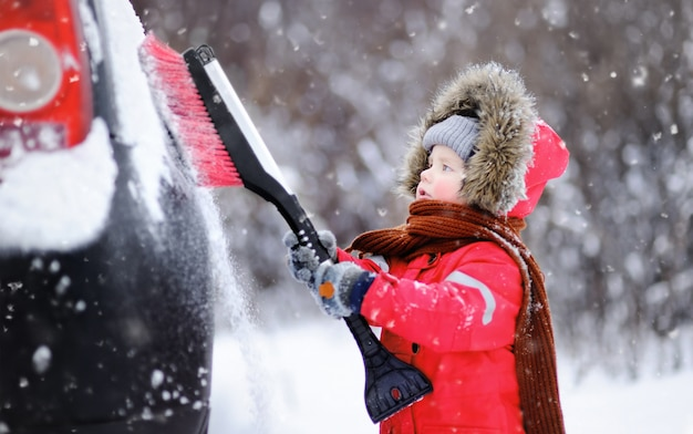 Cute little child helping to brush a snow from a car Premium Photo