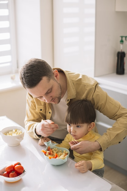 Cute little child and his father eating high view Free Photo