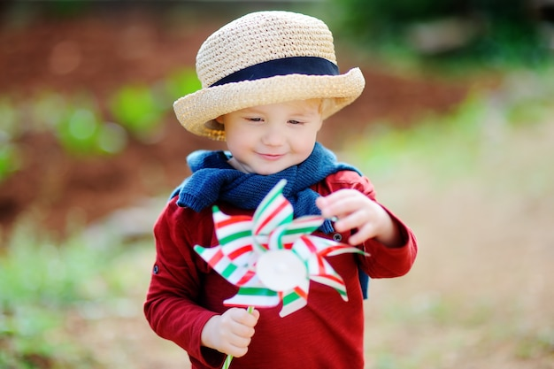Cute little child holding toy windmill. happy toddler boy holding italian flag outdoors Premium Photo