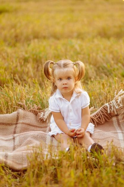 Милый маленький ребенок в белом платье позирует на зеленом поле и Бесплатные Фотографии