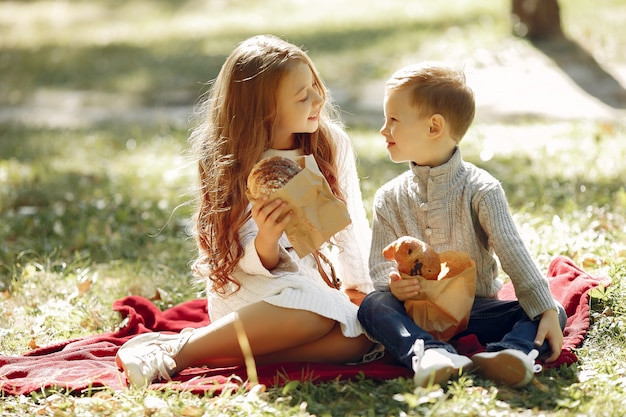 Cute little children sitting in a park with bread Free Photo